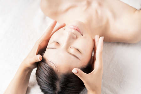 Young woman having her head massaged at the beauty salon