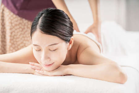 Young woman being massaged in a beauty salon with a bright atmosphere Imagens