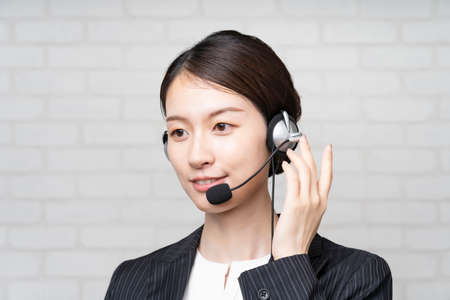 Asian young female operator in a suit wearing a headset and smiling