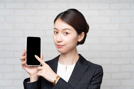 Asian young business woman in suit operating smartphone screen Stock Photo