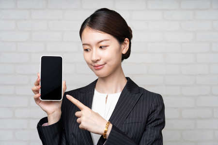Asian young business woman in suit operating smartphone screen