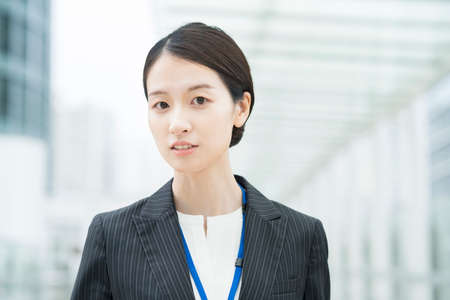 Portrait of a smiling Asian young business woman wearing a suit