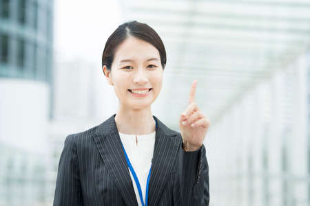 Portrait of Asian young business woman posing with pointing finger