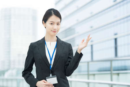 A young Asian business woman in a suit posing for guidance and peace of mind