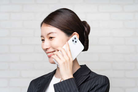 Asian young business woman in a suit talking with the smartphone close to the ear