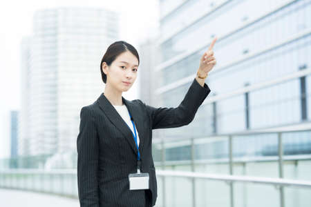 Asian young business woman in a suit pointing diagonally above