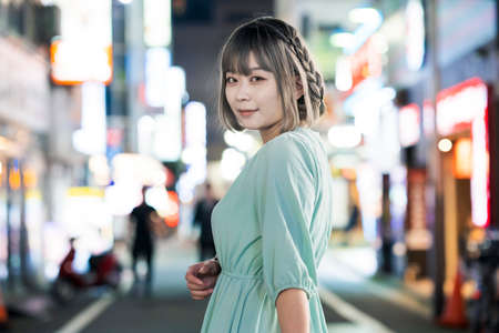 Young woman posing in the glowing cityscape of Tokyo at night