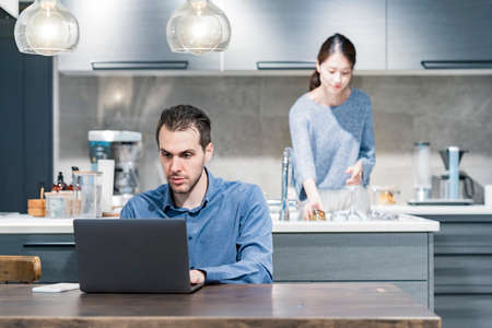 A man working at a dining table and a woman washing dishes in the kitchen