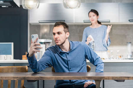 A man who operates a smartphone and an angry woman