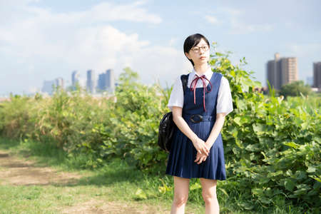 asian high school girl with glasses looking up at the sky