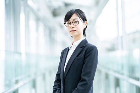 Asian young woman in a suit with a tense look
