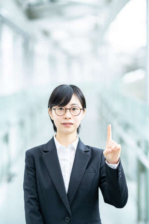 A young woman in a suit posing with her index finger up