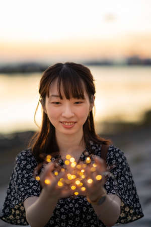 Asian young woman wrapping an illumination light with both hands