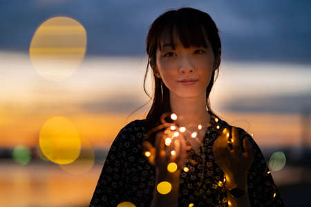 Asian young woman staring at the illumination lights in evening time