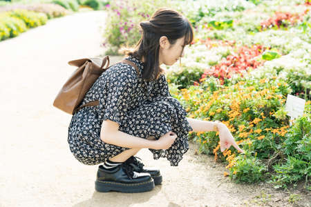 Asian young woman taking a walk in a flower field