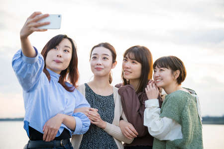 4 young women taking a commemorative photo with a smartphone Imagens