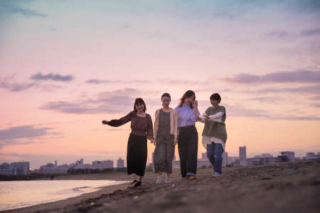 Four young women walking along the sea in the dusk