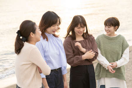 Four asian young women talking happily in the dusk