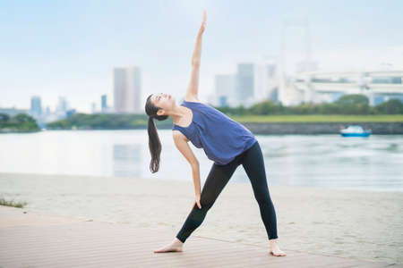 Asian young woman doing yoga on the beach in the city