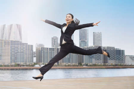 A young business woman in a suit jumping with a smile Banque d'images