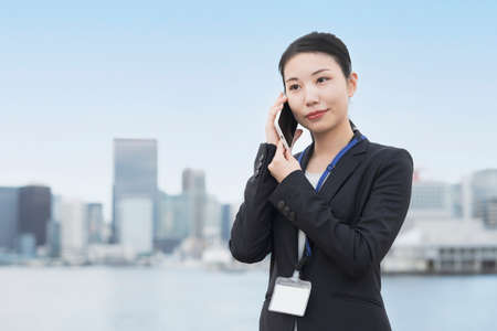 A business woman who talks with her smartphone on her ear Standard-Bild