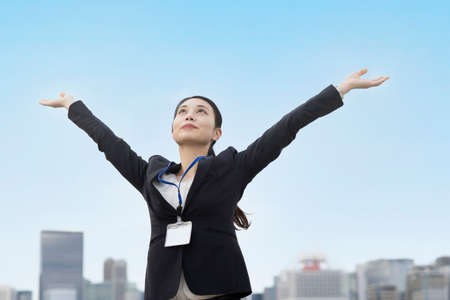 Asian young woman in a suit reaching out and taking a deep breath