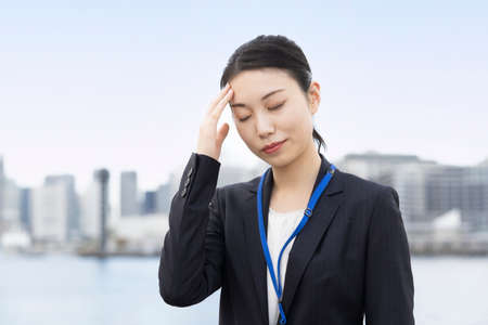 Asian young business woman with a stressed look outodoors