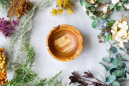 Wooden plate and botanical ornaments set on a marble table