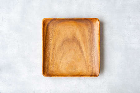 Wooden square empty plate on gray concrete background