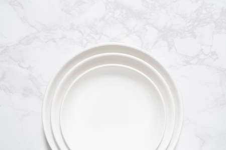 A bird's-eye view of an empty white plate placed on a marble plate