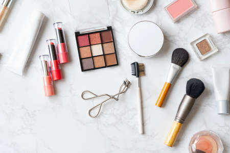 A bird's-eye view of a set of makeup tools placed on a marble plate