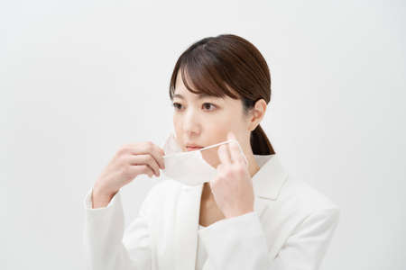 Asian woman in a white suit wearing a mask and white back ground