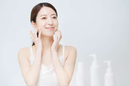 A white bottle with a woman who touches her face for skin care