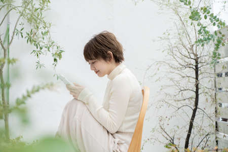 Asian young woman operating a smartphone on chair outdoors