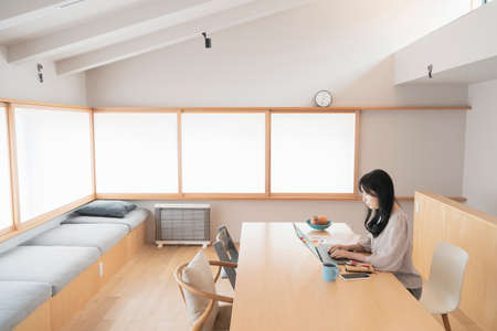 Asian black haired woman working from home using a laptop