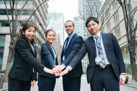A business team holding hands on the streets of the business district