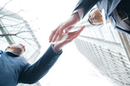 Asian and Caucasian business people shaking hands in suits