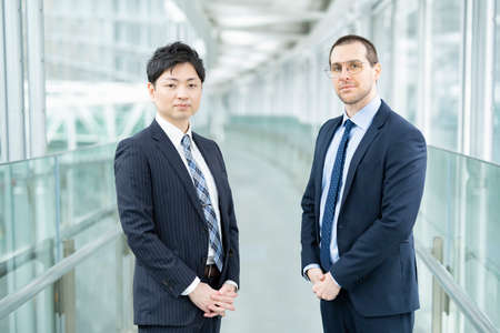 Asian and European businessmen standing at business building