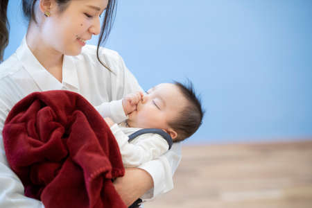 Asian young mom hugging a sleeping baby in the room Standard-Bild