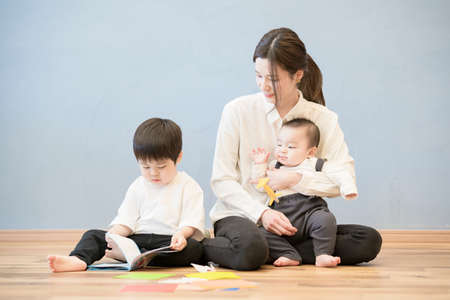 mom and her children who gather and play with each other indoors