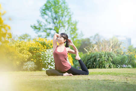 Young woman doing yoga in a green park on fine day Banque d'images