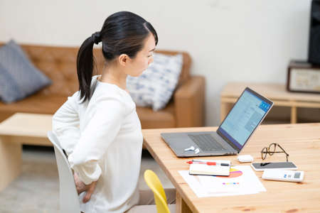 Asian young woman suffering from back pain at work Stock Photo