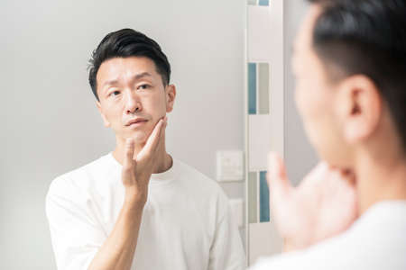 A man who looks in the mirror and checks the condition of his skin