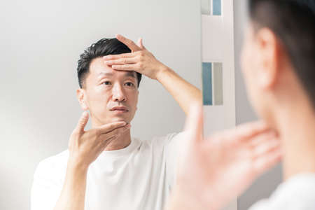 A man who looks in the mirror and checks the condition of his skin Stockfoto