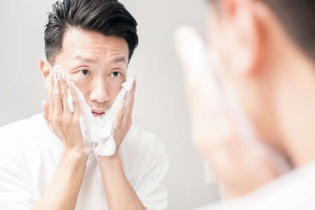 Middle-aged man washing his face with foam at wash basin