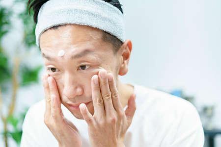 Men applying moisturizing cream to their face in the room Stockfoto