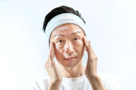 A man who applies cream to his face and white background
