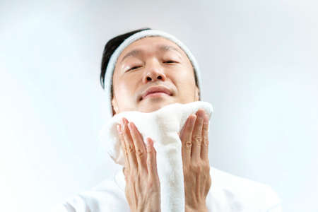 Japanese middle-aged man wiping his face with a towel