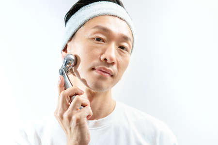 Middle-aged man doing a small face massage with an instrument Stockfoto