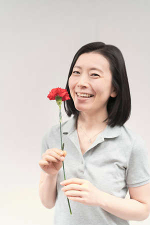 Asian woman smiling with a carnation and white background